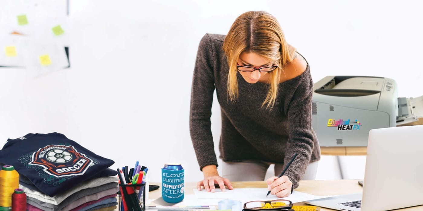 Woman leaning over her desk writing notes in her notebook