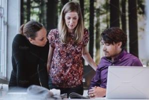 Three employees around a laptop