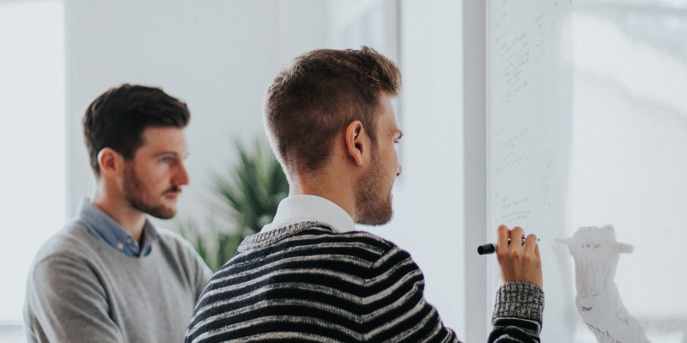 Two men reviewing a whiteboard